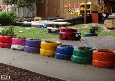 Colorful tire planters line a raised deck