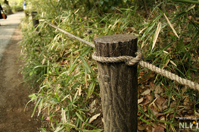 Wooden posts with cable or rope.